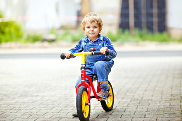 Active blond kid boy in colorful clothes driving balance and learner's bike or bicycle in domestic garden. Toddler child dreaming and having fun on warm summer day. outdoors movement game for children