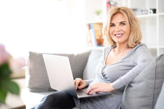 Lächelnde ältere Frau auf der Couch am Laptop schaut in die Kamera