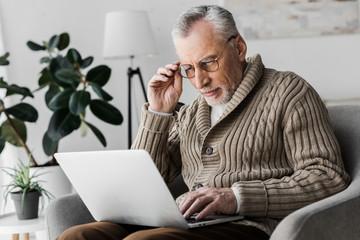 senior man in glasses looking at laptop at home