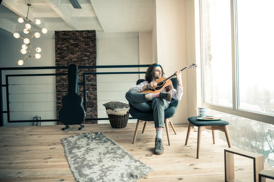 Melancholic stylish musician being alone at home and sitting in bright room