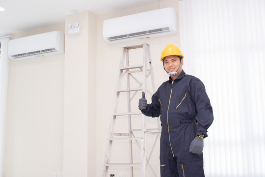 The mechanic Technician are Repairing Air Conditioner in room.