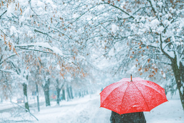 Woman under red umbrella walking in winter snow Wall mural