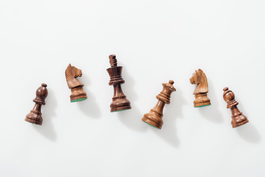 top view of wooden brown chess figures on white background