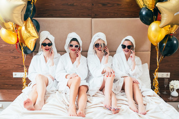 Bathrobe party girls talking on smartphones. Urban females leisure lifestyle. Sunglasses and towel turbans on. Balloons.