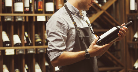 Close-up shot of sommelier holding bottle of red wine in cellar