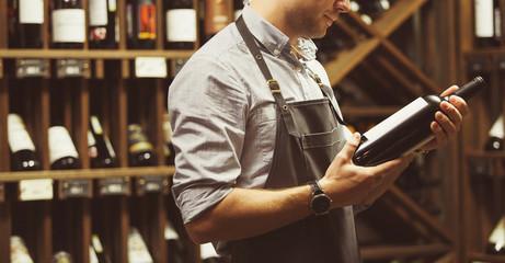Fototapeta Close-up shot of sommelier holding bottle of red wine in cellar
