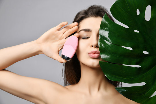 Young pretty woman with closed eyes holds pink face exfoliator brush cleansing device for skin and large green leaf sends a kiss