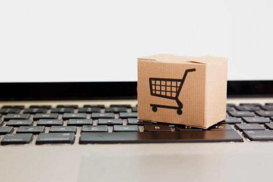 Online shopping . ecommerce and delivery service concept : Paper cartons with a cart or trolley logo on a laptop keyboard, depicts customers order things from retailer sites via the internet