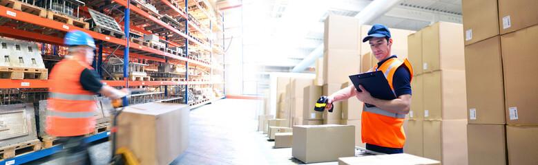 Obraz Lagerung und Logistik im Handel - Arbeiter in einer Logistikhalle - fototapety do salonu