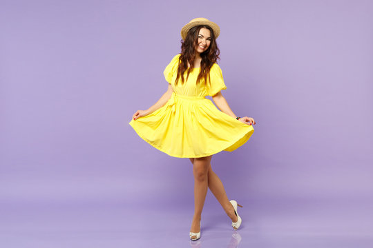 Joyful beautiful young woman in yellow dress summer hat looking camera holding skirt isolated on pastel violet wall background in studio. People sincere emotions lifestyle concept. Mock up copy space.