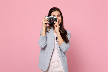 Portrait of smiling young woman in striped jacket taking pictures on retro vintage photo camera isolated on pink pastel wall background. People sincere emotions, lifestyle concept. Mock up copy space.