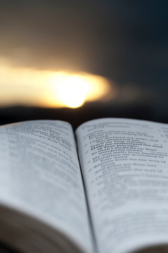 Open Bible with stunning sunset in the background. Close-up. Vertical shot.