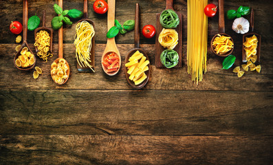 Various pasta on wooden spoons on wooden background Wall mural