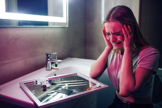 Drugs kill you. Say no to drug. Drug addict cries on drugs background. Drug addicted woman with smeared makeup sits near cocaine lines, syringe in night club's toilet. Find strength to fight