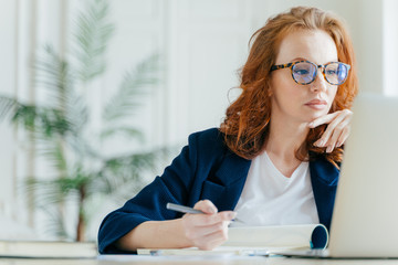 Serious experienced female coach makes records in notepad, focused at screen of laptop computer, has long red hair, wears transparent glasses, watches webinar online. Business and job concept