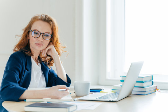 Horizontal shot of confident successful redhead female business owner sits at cabinet, works on laptop computer, writes main theses in notebook, has coffee break, poses in spacious office room