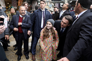 Brazilian President Jair Bolsonaro is partly surrounded by security guards as takes a photo with a girl in Jerusalem's Old City