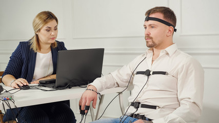 polygraph technician reads questions from a laptop. man connected to the lie detector circuit. Wall mural