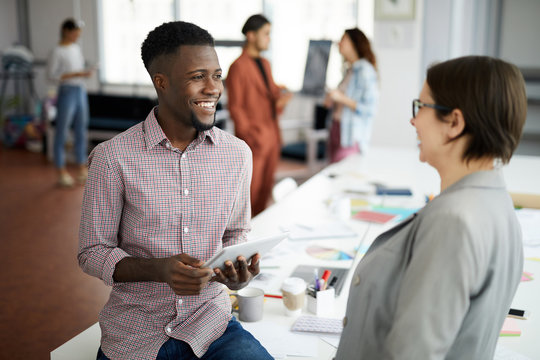 Portrait of handsome African-American man talking to colleague and smiling  while working in modern office, copy space