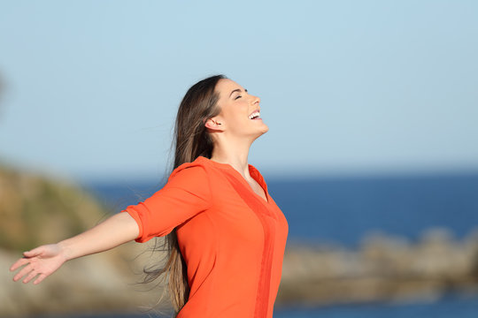 Happy woman in orange breathing fresh air in the coast