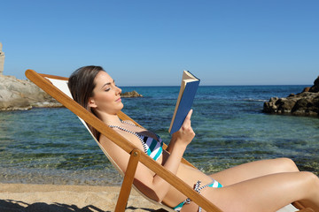 Tourist reading a book on a hammock on the beach