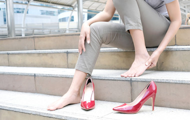 Woman sitting on sofa in room Catch her foot and she has foot pain. Caused by wearing high heels red.Health and beauty concepts