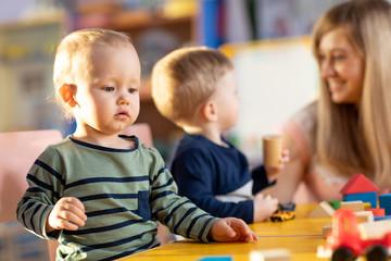 Nursery babies playing blocks toy with teacher in kindergarten