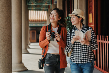 two girls tourist visiting bangkok maining attractions in thailand. women friends travel walking in corridor hallway in chinese temple on sunny day in spring. backpackers smiling with camera and book Fototapete