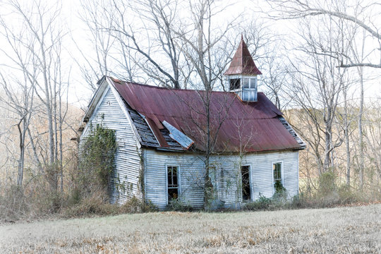 An old country church with a red metal roof, stands in disrepair on a back road in rural Tennessee.