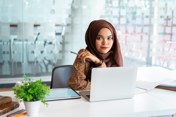 Young asian muslim business woman in smart casual wear discussing business and smiling while sitting in the creative coworking.