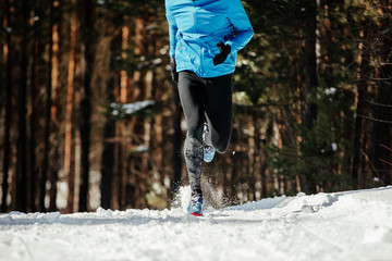 Wall Mural - legs runner athlete running in snow winter trail