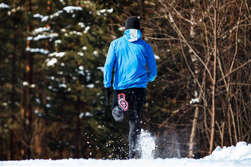 Fototapete - back man runner running winter trail snow flies spray