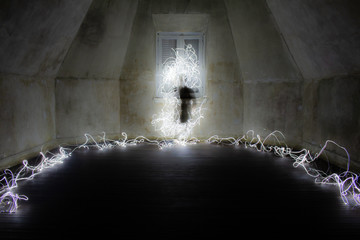 Ghostly figure in an empty room. Light painting photography.