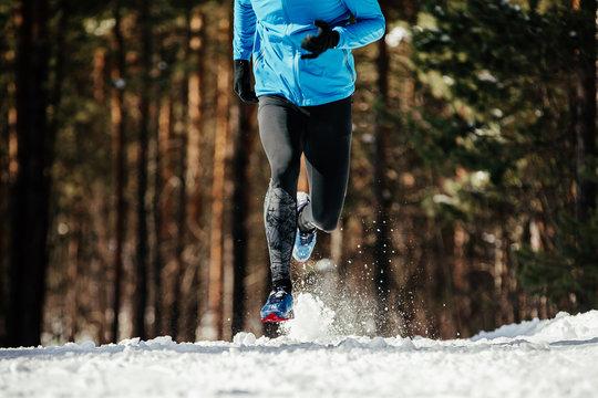 legs man runner running winter trail snow flies spray