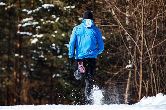back man runner running winter trail snow flies spray