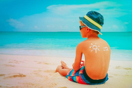 sun protection- little boy with suncream at beach