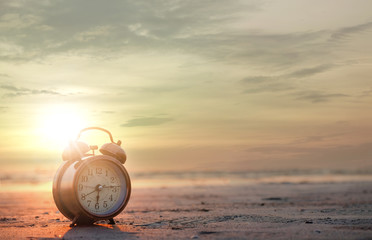 Morning of a new day, alarm clock on the beach sunlight in morning. Health and holiday concept.