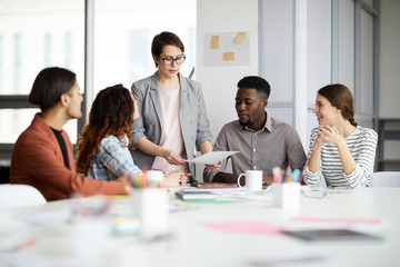 Portrait of successful female manager leading multi-ethnic team in meeting, copy space Wall mural
