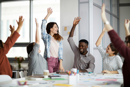 Multi-ethnic team of young businesspeople  raising hands celebrating success in office, copy space