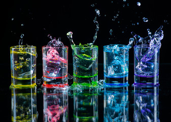 Multicolored glasses filled with alcoholic drinks, with splases of ice cubes falling inside, standing on the mirror surface. Black background. Conceptual, celebrated, commercial design