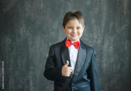 62afc68adbf6 A young guy in a black suit with a red bow tie does like