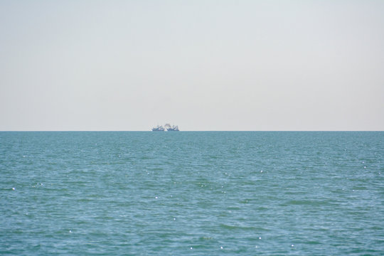 Fishing vessels with exhaust plume visible on the horizon in the Gulf of Mexico off the coast of Florida