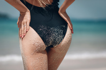 beautiful sports ass in the sand on the background of the sea and the beach in a black swimsuit. closeup