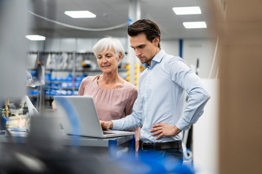 Businessman and senior businesswoman working on laptop in a factory