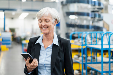 Smiling senior businesswoman looking at cell phone in a factory Wall mural