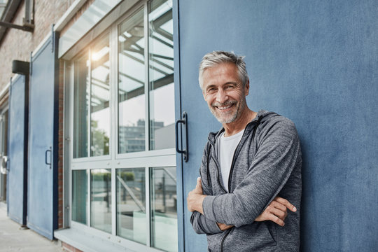 Portrait of smiling man wearing sports clothing standing near building