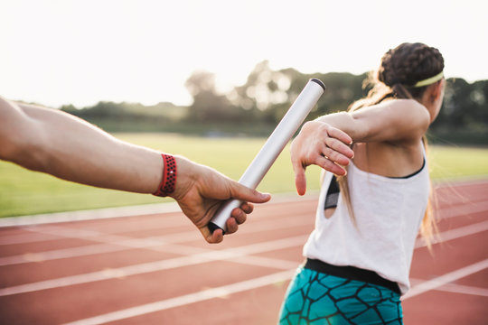 Close up of athlete hand passing baton to woman running on track