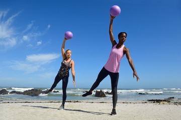 Two women doing fitness exercises with balls on beach