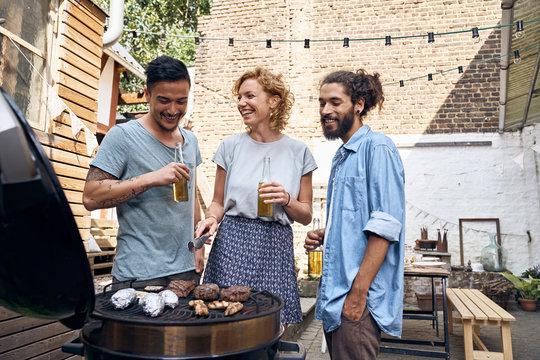 Friends having a barbecue in backyard