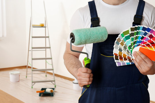 Male decorator with paint roller and color palette samples in empty room, closeup. Space for text